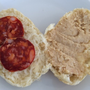 Bread roll with hummus and chorizo